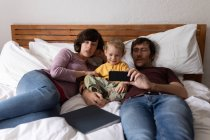 Front view of a young Caucasian father and mother lying on a bed and using a smartphone with their baby — Stock Photo
