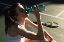Side view close up of a young Caucasian woman drinking water during a tennis game on a sunny day — Stock Photo