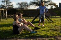 Побочный обзор молодых кавказских женщин и молодого кавказца, сидящего на траве и занимающегося спортом, в то время как молодая кавказская инструктор стоит и разговаривает с ними в открытом спортзале во время тренировочного лагеря — стоковое фото