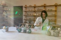 Front view of a young Caucasian female potter sitting at a work table painting a colored glaze on a clay flask in a pottery studio — Stock Photo