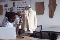 Vista lateral de um jovem estudante de moda afro-americano usando um smartphone para tirar uma foto de um design de jaqueta em um manequim em um estúdio na faculdade de moda — Fotografia de Stock