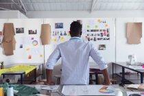 Vue arrière d'un jeune étudiant afro-américain en mode masculine regardant des dessins sur le mur tout en travaillant sur un design regardant des dessins sur un mur dans un studio au collège de mode — Photo de stock