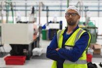 Portrait en gros plan d'un homme d'âge moyen d'une usine de fabrication mixte portant des lunettes et des vêtements de travail regardant une caméra avec les bras croisés dans un entrepôt d'une usine de transformation — Photo de stock