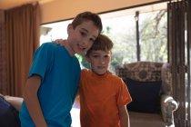 Porträt zweier kaukasischer Jungs im Wohnzimmer zu Hause, die in die Kamera schauen — Stockfoto