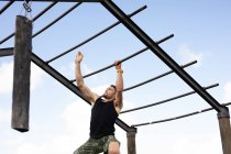 Front view of a young Caucasian man climbing hanging from monkey bars at an outdoor gym during a bootcamp training session — Stock Photo