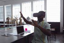 Вид спереди на молодого афроамериканского студента-модельера с поднятыми руками в студии колледжа моды с компьютером и планшетным компьютером на столе перед ним и манекенами на заднем плане — стоковое фото
