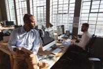 Вид спереди на молодого афроамериканца, сидящего за столом за планшетным компьютером и разговаривающего с молодым коллегой-кавказцем, сидящим за столом за компьютером у окна творческого кабинета — стоковое фото