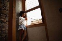 Vue latérale d'une jeune femme métisse debout près d'une fenêtre et regardant dehors tenant une tasse de café — Photo de stock