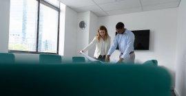 Vista frontal de um jovem afro-americano e uma jovem mulher caucasiana de pé e conversando em uma mesa segurando um plano desenhando no escritório moderno de um negócio criativo — Fotografia de Stock