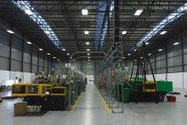 Передній погляд на два ряди обладнання для переробки на складі на заводі. — стокове фото