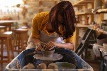 Вид на молодий Кавказький жіночий Поттер, сидячи на гончарних колесо і формуванні глини своїми руками в гончарної студії — стокове фото