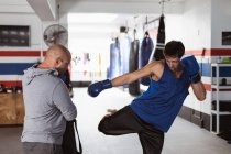 Вид спереди на молодого белого боксёра-боксёра, практикующего удар по коврику, удерживаемого тренером-кавказцем средних лет в боксёрском зале — стоковое фото