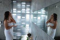 Vista lateral de uma jovem mulher morena caucasiana vestindo uma toalha de banho olhando no espelho segurando um frasco de creme de beleza e aplicando em seu rosto em um banheiro moderno — Fotografia de Stock