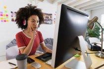 Seitenansicht einer jungen Frau mit gemischter Rasse, die mit Kopfhörern an einem Schreibtisch sitzt und auf einen Computerbildschirm in einem Kreativbüro blickt — Stockfoto