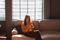 Вид спереди на молодую кавказскую женщину, сидящую на диване, используя смартфон в гостиной креативного офиса, подсвеченного солнечным светом — стоковое фото