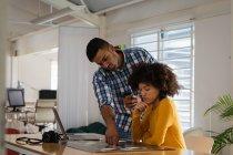 Vue latérale d'un jeune homme de race mixte debout et d'une jeune femme de race mixte assise à un bureau discutant dans un bureau créatif — Photo de stock
