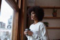 Vista lateral close-up de uma jovem mulher de raça mista em pé por uma janela em casa olhando para fora, segurando uma xícara de café — Fotografia de Stock