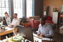 Вид спереди на молодого афроамериканца и молодую кавказку и мужчину, сидящих за партами за компьютерами в креативном офисе — стоковое фото