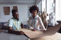 Вид спереди на молодого афроамериканского мужчину и молодую студентку смешанной расы, держащую шаблон, работая над дизайном в студии в колледже моды, с манекенами на заднем плане — стоковое фото