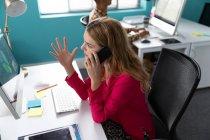 Вигляд збоку закриває молоду кавказьку жінку, яка сидить за столом перед комп'ютером, розмовляючи на смартфоні і жестикулюючи з піднятою рукою — стокове фото