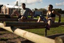 Vue de face d'une jeune femme caucasienne et d'un jeune homme caucasien grimpant à travers des poutres sur un cadre d'escalade dans un gymnase extérieur lors d'une séance d'entraînement de bootcamp — Photo de stock