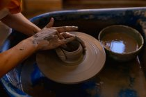Elevated close up of the hands of female potter shaping wet clay into a pot on a potters wheel in a pottery studio — Stock Photo