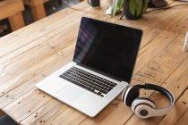 Primer plano de una computadora portátil y un par de auriculares sentados en un escritorio de madera en un espacio de oficina creativo - foto de stock