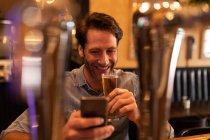 Vista frontale di un giovane caucasico che si rilassa in vacanza in un bar, beve birra e utilizza uno smartphone — Foto stock