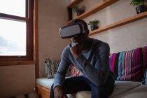 Vista frontale da vicino di un giovane afroamericano che indossa un visore VR seduto su un divano a casa, con il mento appoggiato sulla mano — Foto stock
