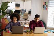 Vista frontale di un giovane uomo di razza mista e una giovane donna di razza mista seduta a una scrivania utilizzando computer portatili in un ufficio creativo — Foto stock