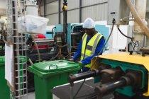 Зворотний вид молодого афроамериканського робітника чоловічої фабрики переміщає зелене на складі на фабриці, в оточенні устаткування й машин. — стокове фото