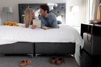 Вид спереди на счастливую молодую кавказскую пару, отдыхающую вместе во время отдыха в гостиничном номере, лежащем на кровати с помощью планшетного компьютера — стоковое фото