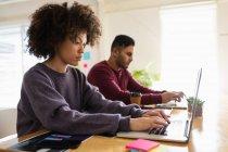 Vista laterale da vicino di un giovane uomo di razza mista e una giovane donna di razza mista seduta a una scrivania usando computer portatili in un ufficio creativo — Foto stock
