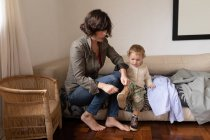 Front view of a young Caucasian mother getting her baby dressed, sitting on a couch — Stock Photo