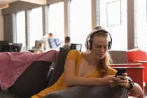 Front view close up of a young Caucasian woman sitting wearing headphones and using a smartphone in the lounge area of a creative office with colleagues working at desks and computers in the background — Stock Photo
