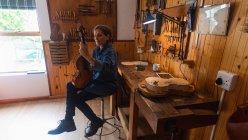 Frontansicht einer älteren kaukasischen Geigenbauerin, die in ihrer Werkstatt eine Geige hält, mit einem Tablet-Computer auf einer Werkbank und Werkzeug an der Wand im Hintergrund — Stockfoto