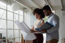 Вид сбоку на молодого человека смешанной расы и молодую женщину смешанной расы, стоящую и проверяющую архитектурный рисунок в креативном офисе — стоковое фото