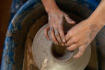 Elevated close up of the hands of female potter shaping wet clay into a pot shape on a potters wheel in a pottery studio — Stock Photo
