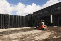 Vista posteriore di un operaio caucasico di mezza età che utilizza un carrello elevatore per spostare una pila di pallet fuori da un magazzino in una fabbrica — Foto stock