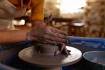 Крупним планом рук жіночий Поттер формування мокрий глина на гончарних колесо в гончарної студії — стокове фото