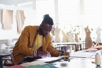 Vue latérale d'un jeune étudiant afro-américain travaillant sur un design à l'aide d'une tablette et d'un stylet dans un studio au collège de mode — Photo de stock