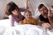 Portrait d'un jeune père et mère caucasiens allongés sur un lit avec leur bébé souriant à la caméra — Photo de stock