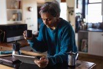 Vista lateral de una mujer mayor caucásica en una cocina tomando café y usando una tableta con armarios de cocina en el fondo - foto de stock