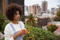 Vista laterale da vicino di una giovane donna di razza mista in piedi fuori su un balcone della città con una tazza di caffè e guardando lontano — Foto stock