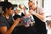 Vista laterale di un parrucchiere caucasico di mezza età, di una parrucchiera mista di mezza età e di una giovane donna caucasica con i capelli colorati in un parrucchiere, riflessi in uno specchio — Foto stock