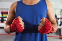 Visão frontal seção média do boxeador masculino em um anel de boxe com as mãos embrulhadas — Fotografia de Stock