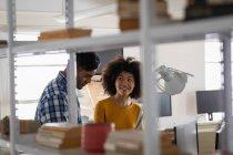 Вид сбоку на молодого человека смешанной расы и молодую женщину смешанной расы, сидящую за столом и обсуждающую в креативном офисе — стоковое фото