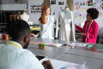 Задний вид молодой афро-американский студент моды сидя и работает над дизайном рисунок в то время как молодые кавказские женщины и смешанной расы студенты моды работать вместе с одеждой на манекен в студии в колледже моды — стоковое фото
