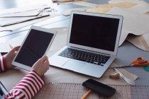 Primer plano de las manos de una estudiante de moda usando una tableta y una computadora portátil mientras trabaja en un diseño en un estudio de la universidad de moda - foto de stock
