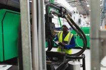 Вид спереди на молодого афроамериканского работника фабрики с планшетом и инспекционным оборудованием на заводе по переработке — стоковое фото